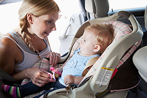 Mother strapping baby into car seat