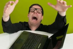 Man crying by broken laptop